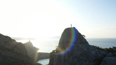 Aerial silhouette of a girl standing on the top of a mountain over the sea at GIF