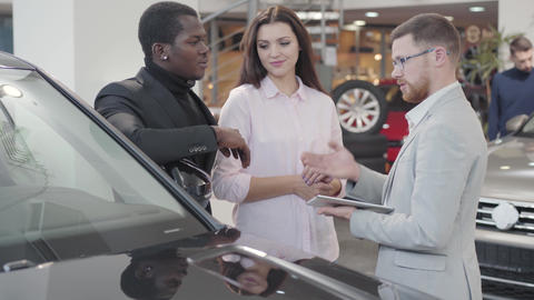Confident Caucasian car dealer standing with clients next to the automobile and Live Action