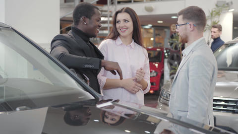 Young multiracial couple taking car keys from salesman in showroom. Young Live Action