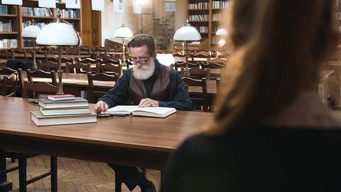 Respected senior bearded man in glasses sitting at the library table while his Archivo
