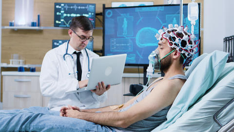 Doctor using his laptop in modern facility for brain analysis GIF