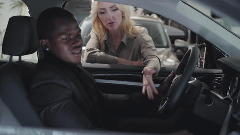 Successful African American man sitting in car salon and talking with female Live Action