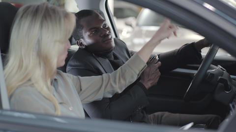 Side view of smiling African American man holding car keys and listening to Live Action