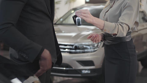 Close-up of male African American hand taking car keys from Caucasian saleswoman Footage