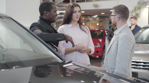 Young Caucasian salesman giving car keys to biracial couple in showroom Footage
