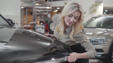 Successful Caucasian businesslady caressing black car hood in showroom. Happy Footage