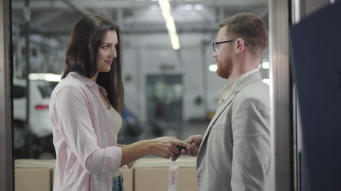 Attractive Caucasian female car dealer giving keys to the confident young Footage
