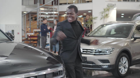 Happy African American man dancing next to his new automobile with car keys Live Action