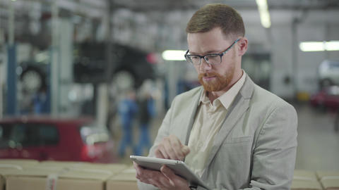 Portrait of redhead Caucasian man in eyeglasses making deal online using his Live Action