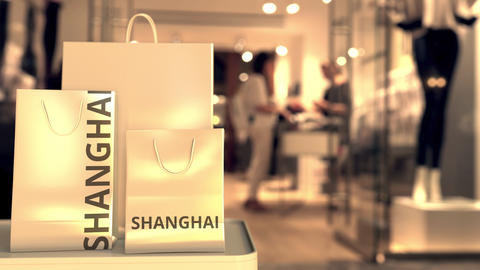 Shopping bags with SHANGHAI text against blurred store. Chinese retail related Footage