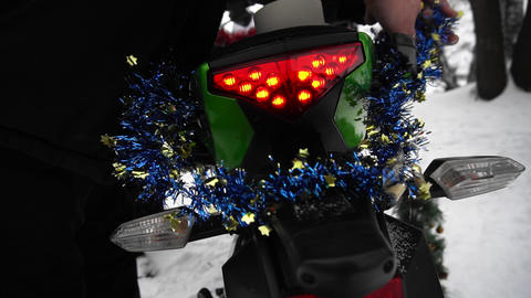 Biker man decorates with tinsel his motorcycle in winter holidays hands closeup Live Action