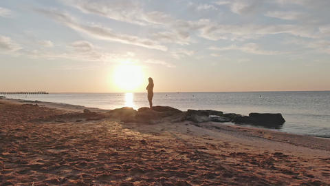 Silhouette of a woman who stands on the seashore at dawn The camera slowly Live Action