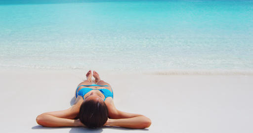 SEAMLESS LOOP VIDEO: Beach travel woman sunbathing relaxing lying down at beach Footage