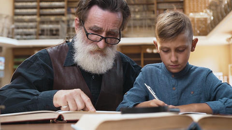 Close up of intelligent bearded grandfather with handsome teenage schoolboy Archivo