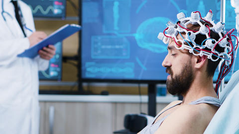 Patient with brainwaves scanning headset sitting on bed GIF