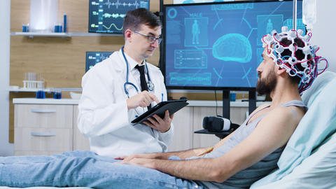 Doctor in brain research staying next to patient bed and typing on tablet ビデオ