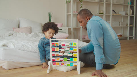 Dad teaching son alphabet with educational abc toy Archivo