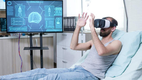 Patient in a neuroscience centre wearing vr goggle and making hand gestures GIF