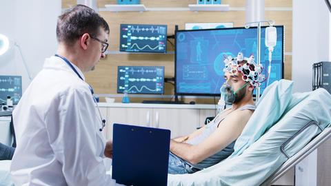 Patient in a neurology centre wearing brainwaves scanning headset ビデオ