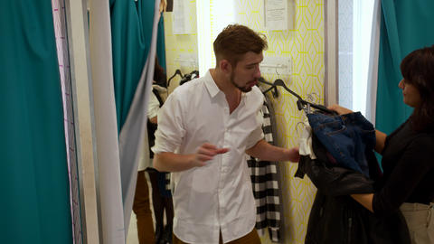 Woman gives her man clothes in the fitting room Archivo