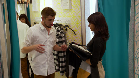 Young woman brings clothes to man in fitting room Archivo
