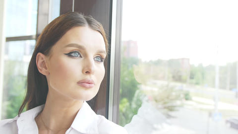 The face of a woman who looks at the city street through the window Her face is Live Action