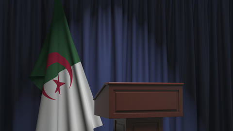 Flag of Algeria and speaker podium tribune. Political event or statement related Live Action