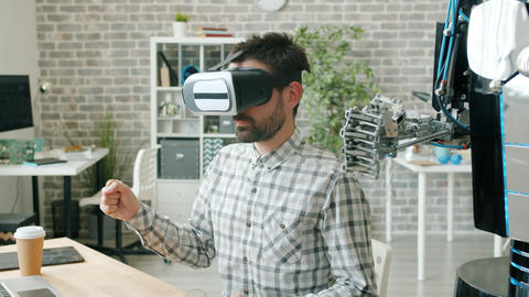 Robot moving fingers like guy in virtual reality glasses, person testing machine Archivo