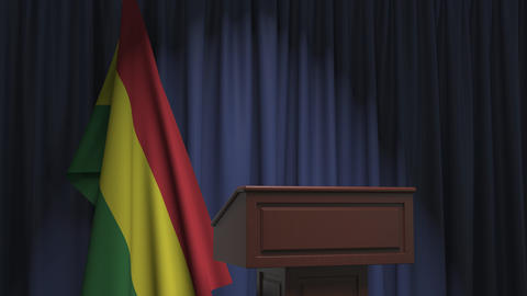 Flag of Bolivia and speaker podium tribune. Political event or statement related Live Action