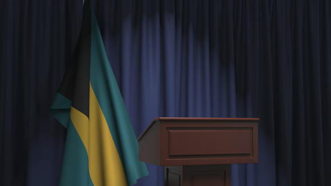 Flag of Bahamas and speaker podium tribune. Political event or statement related Live Action