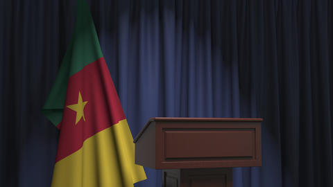 Flag of Cameroon and speaker podium tribune. Political event or statement Live Action