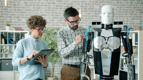 Man and woman testing modern human-like robot in laboratory using tablet Archivo