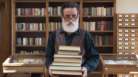 Esteemed senior bearded man holding a lot of books in his hands and posing on Archivo