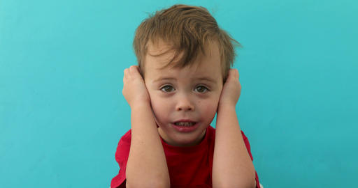 Worried child closing ears Archivo