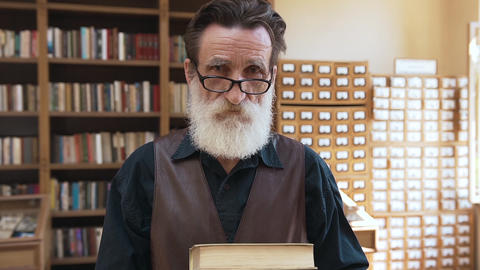 Esteemed old bearded man in glasses holding books in hands and looking at camera ビデオ