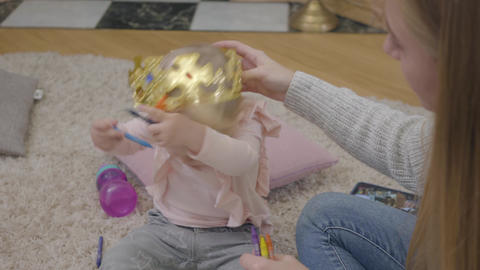 Close-up of young Caucasian mother trying to put toy crown on daughter's head Footage