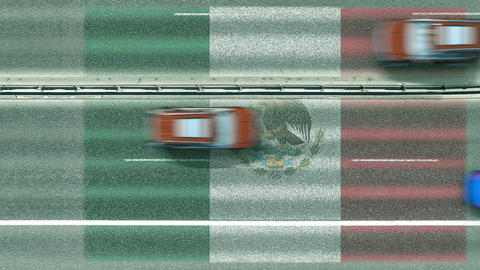 Aerial top down view of cars revealing flag of Mexico on the road. Traveling Footage
