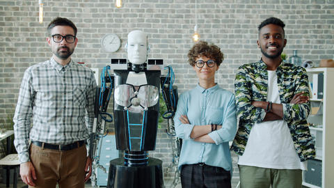 Portrait of smiling engineers and robot looking at camera standing in office Archivo