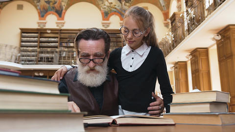 Intelligent old bearded grandfather in glasses reading book with his cute teen Archivo