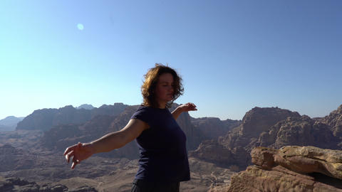 Inspirational woman enjoy life, dancing outdoors at the edge of mountains Live Action