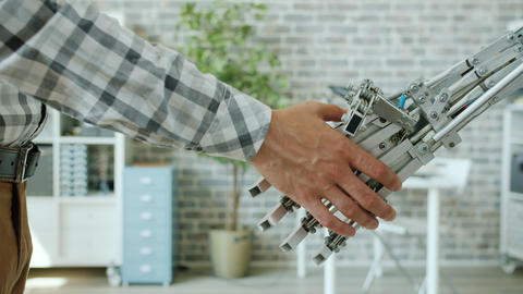 Close-up shot of man and intelligent robot shaking hands in office room Archivo