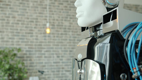 Close-up tilt-up of modern human-like robot in contemporary office room Archivo