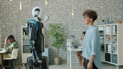 Cheerful girl shaking hand to intelligent droid smiling enjoying new technology Archivo