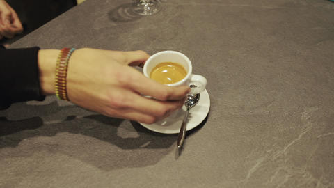 Close-up of hand placing hot ceramic white coffee cup with smoke on saucer over Archivo