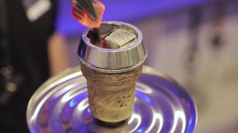 Man preparing hookah bowl and coald for smoking shisha. Hot embers for a hookah Archivo