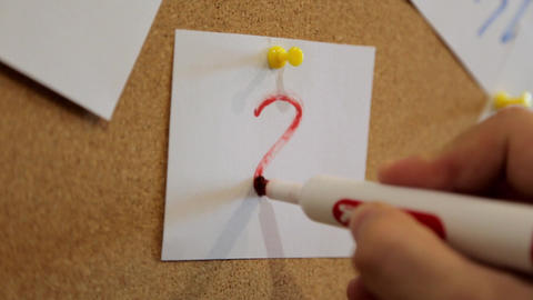 Search concept. A man writes with a red marker a question mark on a white sheet Footage