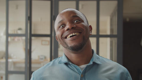 Cheerful african guy laughing sincerely indoors GIF