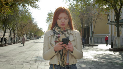 A young girl stands on a city street. Holding a smartphone, typing a text Footage