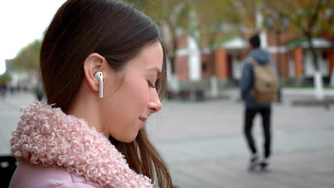 Lovely young girl is listening to music through wireless white headphones. Sits Footage
