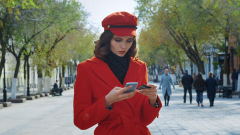 A young girl stands on a city street. Holding a smartphone and a bank card Footage